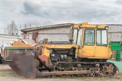 Alter rostiger gelber verlassener Traktor mit Eimer lizenzfreie stockbilder