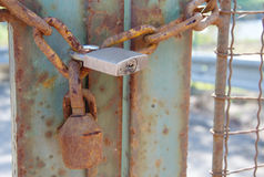 Alter rostiger Metallschmutzverschluß auf dem angeketteten Zaun mit dem neuen Verschluss stockbild