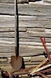 Alter rostiger Spaten steht gegen eine Blockhauswand still Lizenzfreie Stockbilder