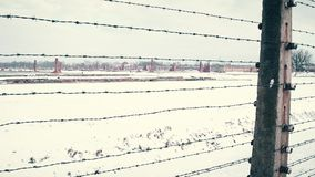 Alter rostiger Stacheldrahtzaun und entfernte ruinierte Kasernen des Konzentrationslagers im Schnee steadicam 4K Schuss Lizenzfreie Stockbilder