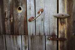 Alter rostiger Verschluss, der an der grauen Holztür hängt Stockbilder