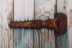 Alter rostiger Verschluss, der an der grauen Holztür hängt Lizenzfreies Stockfoto
