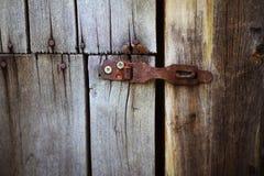 Alter rostiger Verschluss, der an der grauen Holztür hängt Stockfotos