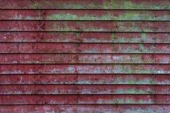 Alter roter Bretterzaun des Schmutzes mit grünen Moosmustern - Beschaffenheit/Hintergrund der hohen Qualität stockbild
