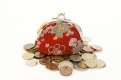 Alter roter Geldbeutel und Münzen Stockfoto