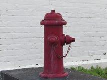 Alter roter Hydrant gegen weiße Backsteinmauer Stockbilder