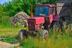 Alter roter rostiger Traktor stockbild