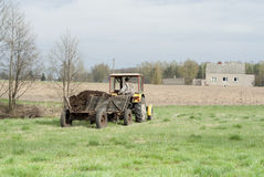 Alter rustikaler Traktor, der Düngemittel liefert. Stockbild