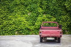 Alter Rusty Red Truck Parked im leeren Los Verlassene Aufnahme mit den Stangen-Schienen-Anrichten, die eine belaubte bedeckte Wan stockbilder
