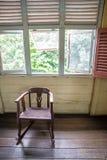 alter Schaukelstuhl unter einigen Fenstern Lizenzfreies Stockfoto