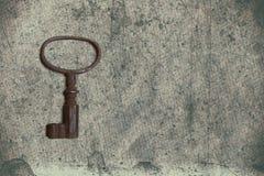 Alter Schlüssel auf dem alten strukturierten Papier mit natürlichen Mustern Stockfotos