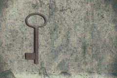 Alter Schlüssel auf dem alten strukturierten Papier mit natürlichen Mustern Lizenzfreie Stockfotografie