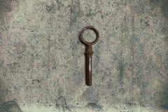 Alter Schlüssel auf dem alten strukturierten Papier mit natürlichen Mustern Lizenzfreies Stockbild