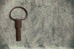 Alter Schlüssel auf dem alten strukturierten Papier mit natürlichen Mustern Stockbilder