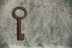 Alter Schlüssel auf dem alten strukturierten Papier mit natürlichen Mustern Lizenzfreie Stockfotos