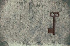 Alter Schlüssel auf dem alten strukturierten Papier mit natürlichen Mustern Stockbild