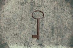 Alter Schlüssel auf dem alten strukturierten Papier mit natürlichen Mustern Stockfotografie