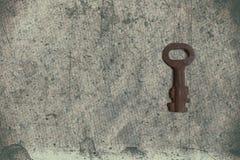 Alter Schlüssel auf dem alten strukturierten Papier mit natürlichen Mustern Stockfoto