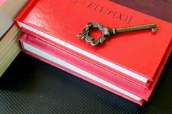 Alter Schlüssel auf roten Büchern Stockbild