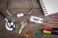Alter Schlüssel mit children& x27; s-Gesundheit Text Hölzerner Beschaffenheitshintergrund w Lizenzfreies Stockbild