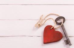 Alter Schlüssel mit einem Herzen auf weißem Holz Stockfotografie