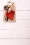 Alter Schlüssel mit einem Herzen auf weißer Vertikale Stockbild