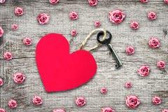 Alter Schlüssel mit einem Umbau aus Papierherzen auf einem Holztisch heraus Kopieren Sie Platz Beschneidungspfad eingeschlossen V lizenzfreies stockfoto