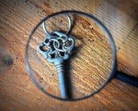 Alter Schlüssel mit einer Lupe lizenzfreies stockbild