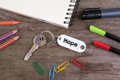 Alter Schlüssel mit Hoffnungs-Text Hölzerner Beschaffenheitshintergrund mit Bleistiften, Stockfotografie