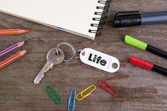 Alter Schlüssel mit Leben-Text Hölzerner Beschaffenheitshintergrund mit Bleistiften, Stockfoto