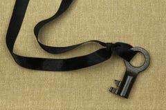 Alter Schlüssel mit Trauerflor auf natürlichem Leinen Lizenzfreie Stockfotos