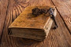 Alter Schlüssel mit Buch Stockbilder