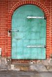 Alter Schmutz, der grüne Stahltür mit Backsteinmauer schaut Lizenzfreie Stockfotos