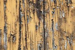 Alter Schmutz getragenes hölzernes Brett mit gebrochener und abgezogener brauner gelber Farbe Stockfoto