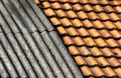 Alter schmutziger geverwitterter gewellter Schiefer und Keramikfliesen schichten Dach Stockbild