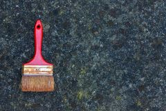 Alter schmutziger roter Pinsel auf Steinhintergrund Stockbilder