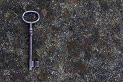 Alter schmutziger Weinlesemetallschlüssel auf Steinhintergrund Lizenzfreies Stockbild