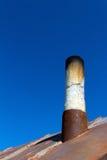 Alter Schornstein aus dem rostigen Eisendach heraus Lizenzfreie Stockbilder