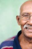 Alter schwarzer Mann mit Gläsern und dem Schnurrbartlächeln Stockbild