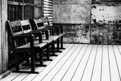 Alter Schwarzweiss-Holzstuhl in der Eisen-Wandweinlese des alten hölzernen Raumes alten Lizenzfreies Stockfoto