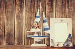 Alter Seerahmen mit Starfish auf Holztisch und hölzernem Hintergrund Weinlese gefiltertes Bild Stockfotografie
