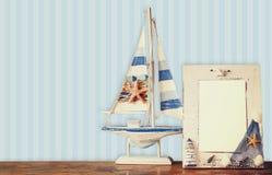 Alter Seerahmen mit Starfish auf Holztisch und Retro- blauem Hintergrund Weinlese gefiltertes Bild Stockfotos