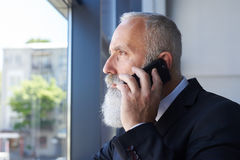 Alter Sir mit grauem Bart sprechend am Telefon beim windo heraus schauen Stockbild