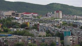 Alter sowjetischer städtebaulicher Siedlungsbau auf Hintergrund von Bergen und von grünem Wald stock footage