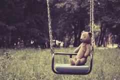Alter Spielzeugteddybär, der auf Schwingen im Park sitzt Stockbilder