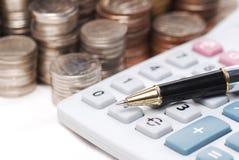 Alter staubiger Kugelschreiber auf Taschenrechner mit Stapel prägt Hintergrund Lizenzfreies Stockfoto