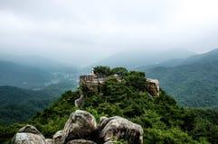 Alter Stein-Buddha steht auf großem Felsen eines Berges Lizenzfreie Stockfotos