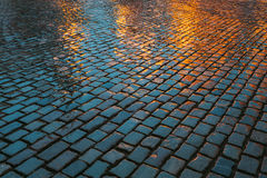 Alter Straßen-Kopfstein-Zusammenfassungs-Hintergrund Nasse Steine am Abend stockbild