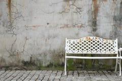 Alter Stuhl auf dem Zementwandhintergrund Stockfotos