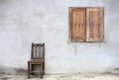 Alter Stuhl gegen alte Wand mit Fenster Lizenzfreie Stockfotografie